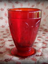 red glass, ornate drink glass, leaf on bottom